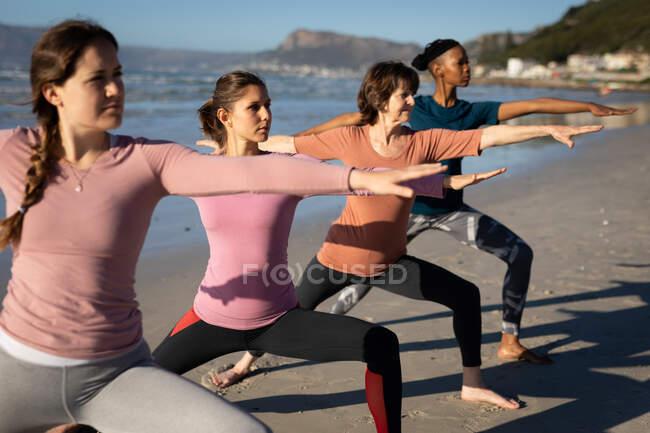 Вид сбоку на многоэтническую группу подруг, наслаждающихся упражнениями на пляже в солнечный день, практикующих йогу стоя в военной асане. — стоковое фото