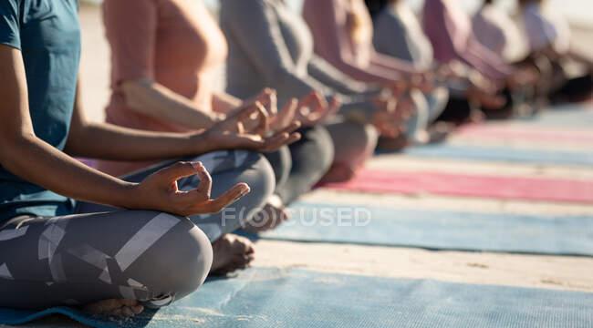 Seitenansicht Mittelteil einer Gruppe von Freundinnen, die an einem sonnigen Tag am Strand Sport treiben, Yoga praktizieren, in Yogaposition mit Mudra-Händen sitzen, meditieren. — Stockfoto