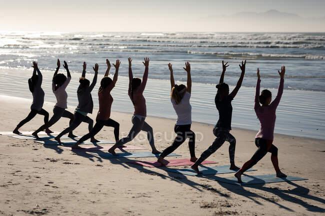 Вид сзади на многонациональную группу подруг, занимающихся спортом на пляже в солнечный день, практикующих йогу, стоящих в позиции йоги. — стоковое фото