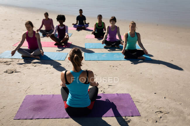 Rear view of Caucasian woman, wearing sports clothes, sitting on a yoga mat, practicing yoga with a group of multi-ethnic female friends sitting facing her on the sunny beach. — Stock Photo