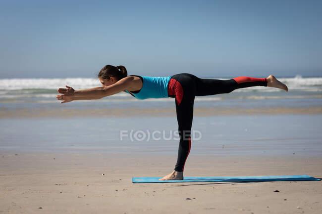 Вид сбоку на кавказскую привлекательную женщину, в спортивной одежде, практикующую йогу, стоящую в одной ноге в позиции йоги, на солнечном пляже. — стоковое фото