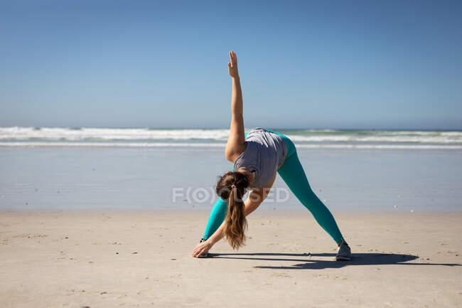 Вид спереди на кавказскую привлекательную женщину с длинными волосами, в спортивной одежде, практикующую йогу, растянувшуюся в позиции йоги, на солнечном пляже. — стоковое фото