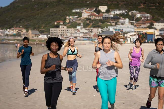 Vista frontal de un grupo multiétnico de amigas disfrutando de hacer ejercicio en una playa en un día soleado, corriendo a la orilla del mar. - foto de stock