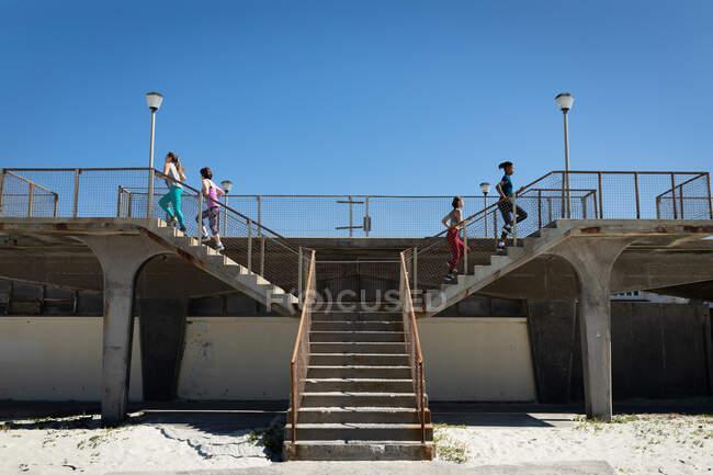 Vista laterale di un gruppo multietnico di amiche che si esercitano su una spiaggia in una giornata di sole, correndo su per le scale per il lungomare. — Foto stock