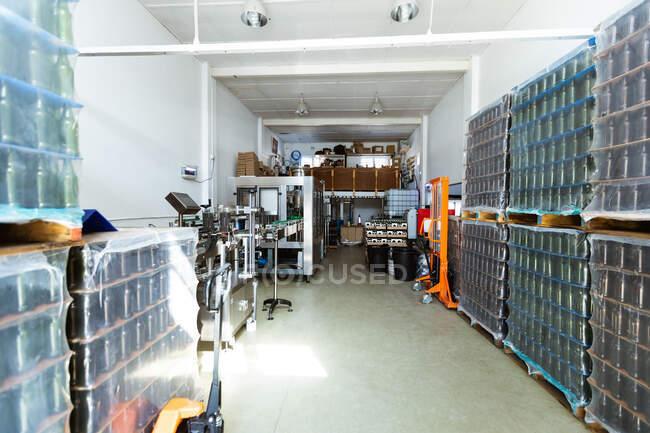 Стиллеры с бутылочным пивом, покрытые пластиковым накладным покрытием, размещены вдоль стен в небольшом отсеке для хранения пивоварни, ожидая доставки. — стоковое фото