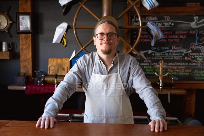 Портрет кавказького бармена в білому фартусі, робота в мікропивоварні паб, стоячи з руками в барі і дивлячись прямо в камеру.. — стокове фото