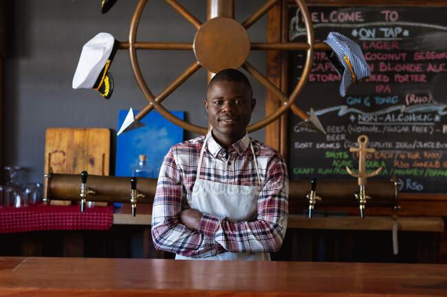 Портрет афроамериканского бармена в белом фартуке, работающего в пивоварне, стоящего со скрещенными руками и смотрящего прямо в камеру. — стоковое фото