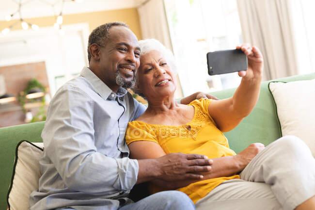 Счастливая пожилая афроамериканская пара в своей гостиной, сидящая на диване, женщина, держащая смартфон, оба смотрят на телефон вместе, делают селфи и улыбаются, пара изолируется во время пандемии coronavirus covid19 — стоковое фото