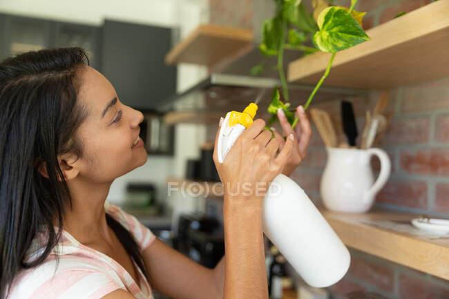 Mujer de raza mixta pasando tiempo en casa autoaislante y distanciamiento social en cuarentena de bloqueo durante coronavirus covid 19 epidemia, el cuidado de sus plantas. - foto de stock