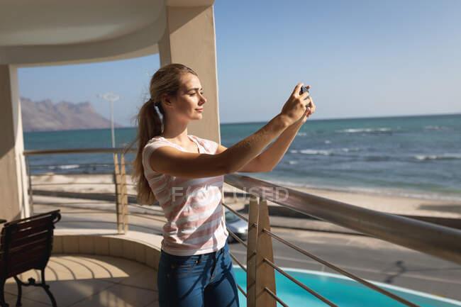 Donna caucasica in piedi su un balcone, che tiene uno smartphone e si fa un selfie. Distanziamento sociale e autoisolamento in quarantena. — Foto stock