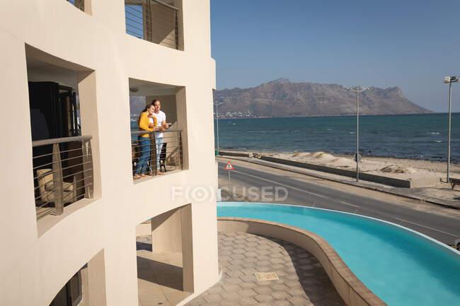 Casal caucasiano em pé em uma varanda, abraçando. Distanciamento social e auto-isolamento em quarentena. — Fotografia de Stock