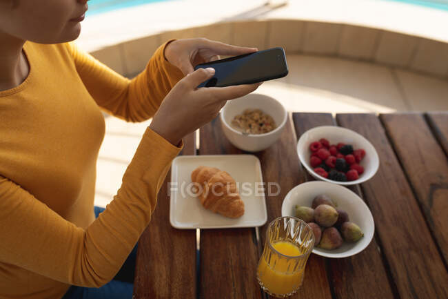 Caucasian woman sitting by a table, taking a photo of breakfast with her smartphone. Social distancing and self isolation in quarantine lockdown. — Stock Photo