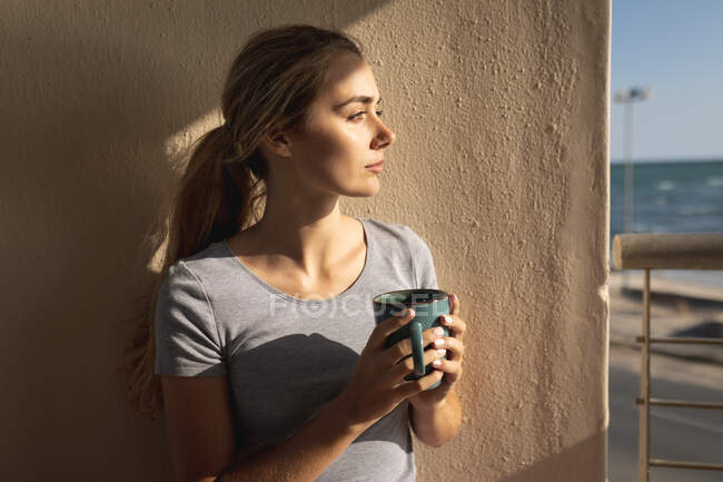 Caucasian woman standing on a balcony, holding a cup of coffee and looking away. Social distancing and self isolation in quarantine lockdown. — Stock Photo