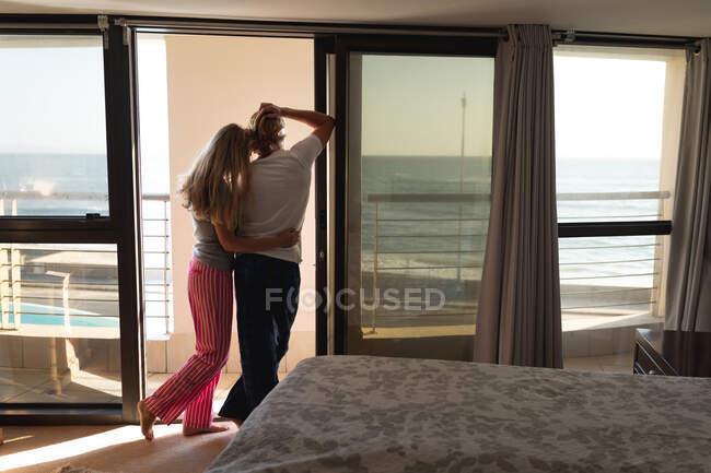Pareja caucásica de pie en un balcón, abrazándose. Distanciamiento social y autoaislamiento en cuarentena. - foto de stock