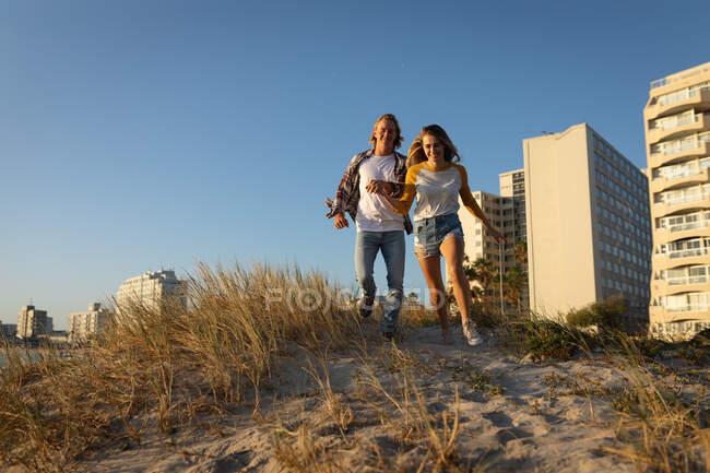 Coppia caucasica che corre su una duna di sabbia erbosa al sole tenendosi per mano, godendo di una vacanza al mare con edifici moderni sullo sfondo — Foto stock