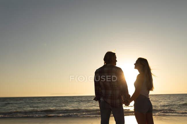 Coppia caucasica in piedi su una spiaggia durante un tramonto, che si tiene per mano e si guarda — Foto stock