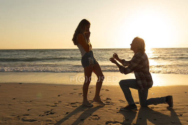 Caucasian couple enjoying their time at a beach during sunset, a man is kneeling and proposing to a woman — Stock Photo