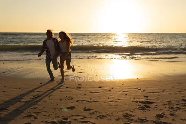 Coppia caucasica in vacanza correndo su una spiaggia durante un tramonto, tenendosi per mano, con il sole al tramonto riflesso sul mare e la sabbia dietro di loro — Foto stock