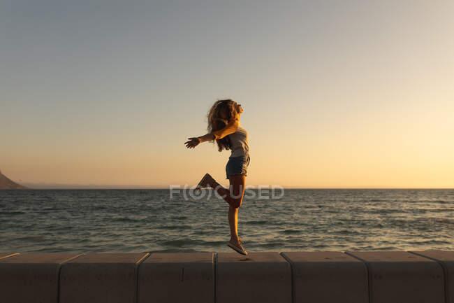 Donna caucasica in vacanza godendo il suo tempo su una passeggiata sulla spiaggia durante un tramonto, saltando e allargando le braccia, il sole che tramonta sul mare sullo sfondo — Foto stock