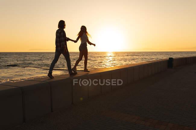 Coppia caucasica silhouettata che cammina su una passeggiata in riva al mare al tramonto, tenendosi per mano. Romantica coppia di vacanze al mare — Foto stock