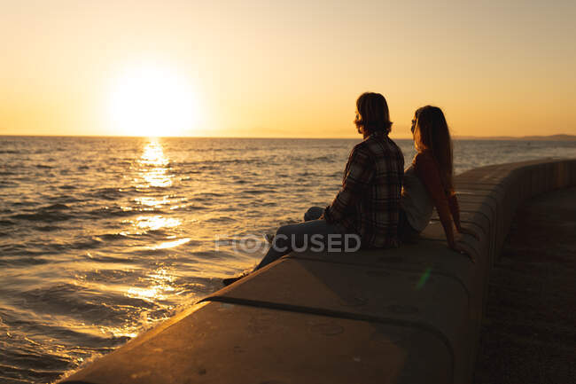 Кавказская пара, сидящая вместе на набережной у моря на закате, смотрит в море. Романтическая пляжная пара — стоковое фото