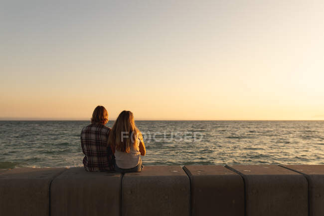 Rückansicht eines kaukasischen Paares, das bei Sonnenuntergang zusammen auf einer Strandpromenade am Meer sitzt und aufs Meer blickt. Romantische Strandurlauber — Stockfoto