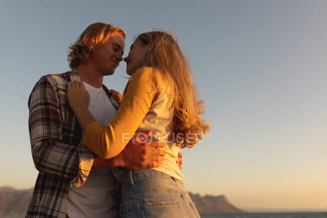 Caucasian couple standing on a promenade during sunset, embracing and kissing. Romantic couple seaside beach holiday — Stock Photo