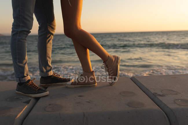 Baixa seção de casal em pé em um passeio à beira-mar ao pôr-do-sol, de frente para o outro e abraçando ou beijando. Casal romântico de férias à beira-mar — Fotografia de Stock