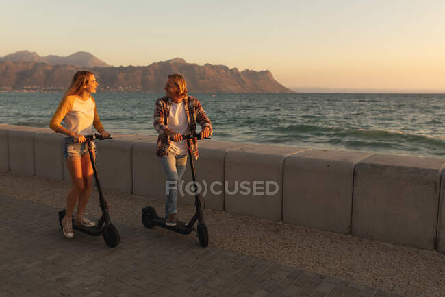 Coppia caucasica cavalcando e-scooter su una passeggiata durante il tramonto, guardarsi, rilassarsi durante una vacanza al mare attiva — Foto stock