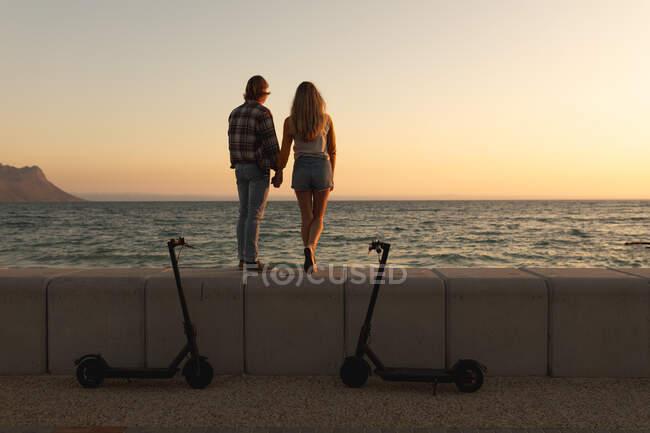 Vista posteriore della coppia caucasica in piedi su una passeggiata sul mare al tramonto con e-scooter parcheggiati, tenendosi per mano e guardando il mare. Coppia sulla romantica vacanza al mare al mare — Foto stock