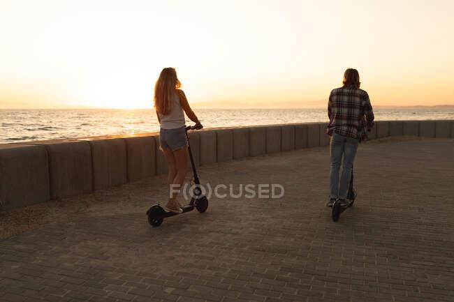 Vista posteriore della coppia caucasica cavalcando e-scooter su una passeggiata sul mare al tramonto, rilassante durante una vacanza attiva al mare — Foto stock