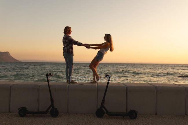 Coppia caucasica in piedi su una passeggiata in riva al mare, con e-scooter parcheggiati, che si tengono per mano e si guardano. Coppia sulla romantica vacanza al mare al mare — Foto stock