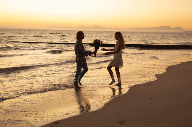 Caucasian couple enjoying time on a beach during sunset, a man is giving a woman a bouquet of flowers — Stock Photo