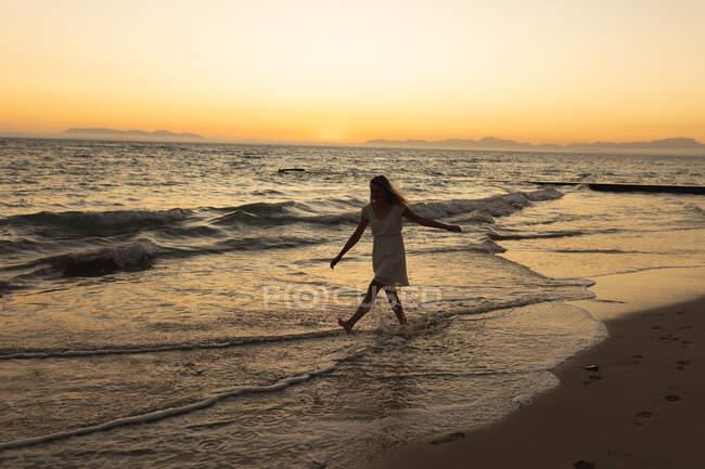 Donna caucasica su una spiaggia che cammina a piedi nudi nell'acqua di mare poco profonda al tramonto, rilassandosi durante una vacanza al mare attiva — Foto stock