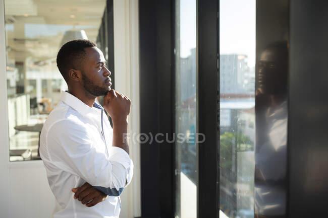 Африканский бизнесмен в белой рубашке, работает в современном офисе, смотрит в окно, трогает подбородок и думает: — стоковое фото