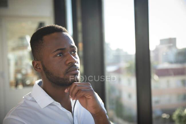 Афро-американский бизнесмен в белой рубашке, работает в современном офисе, стоит у окна, трогает подбородок и думает: — стоковое фото