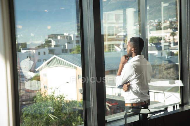 Un uomo d'affari afroamericano, indossa una camicia bianca, lavora in un ufficio moderno, guarda attraverso una finestra, tocca il mento e pensa: — Foto stock
