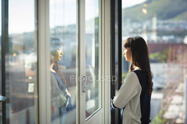 Uma mulher de negócios asiática trabalhando em um escritório moderno, olhando através de uma janela e pensando, cruzando os braços, em um dia ensolarado — Fotografia de Stock