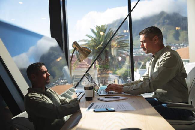Un uomo d'affari caucasico che lavora in un ufficio moderno, seduto alla scrivania e utilizzando un computer portatile, in una giornata di sole — Foto stock