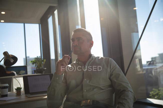 Кавказький бізнесмен, який працює в сучасному офісі, сидить за столом, тримаючи ручку, озираючись і думаючи, в сонячний день. — стокове фото