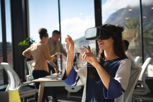 An Asian businesswoman working in a modern office, wearing VR headset, touching virtual interactive screen, with her colleagues working in the background — Stock Photo