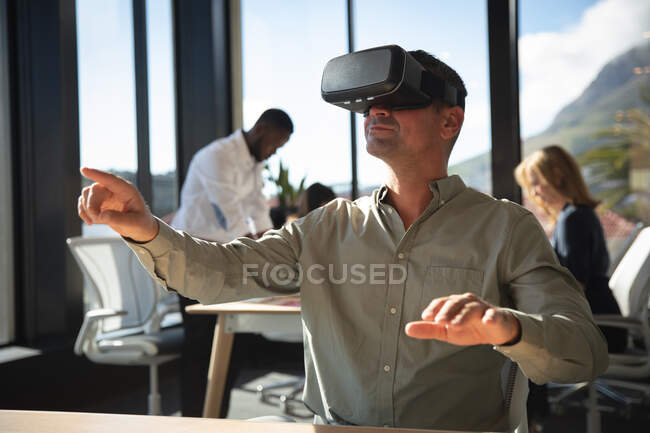 A Caucasian businessman working in a modern office, wearing VR headset, touching virtual interactive screen, with his colleagues working in the background — Stock Photo