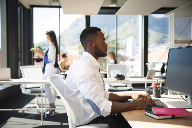 An African American businessman working in a modern office, sitting at a desk and using a computer, with his colleagues working in the background — Stock Photo