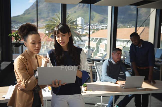 Una razza mista e una donna d'affari asiatica che lavora in un ufficio moderno, usando un computer portatile e parlando, con i loro colleghi che lavorano in background — Foto stock