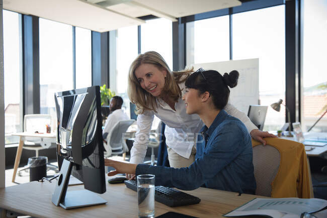 A Caucasian and an Asian businesswomen working in a modern office, using a laptop computer and talking, with their colleagues working in the background — Stock Photo