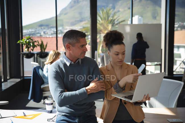 Una donna d'affari di razza mista e un uomo d'affari caucasico che lavorano in un ufficio moderno, usando un computer portatile e parlando, con i loro colleghi che lavorano in background — Foto stock