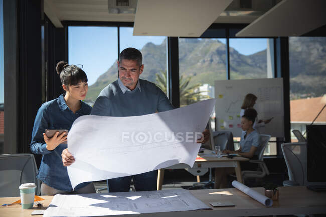 An Asian businesswoman and a Caucasian businessman working in a modern office, standing by a desk, looking at plans and talking, with their colleagues working in the background — Stock Photo