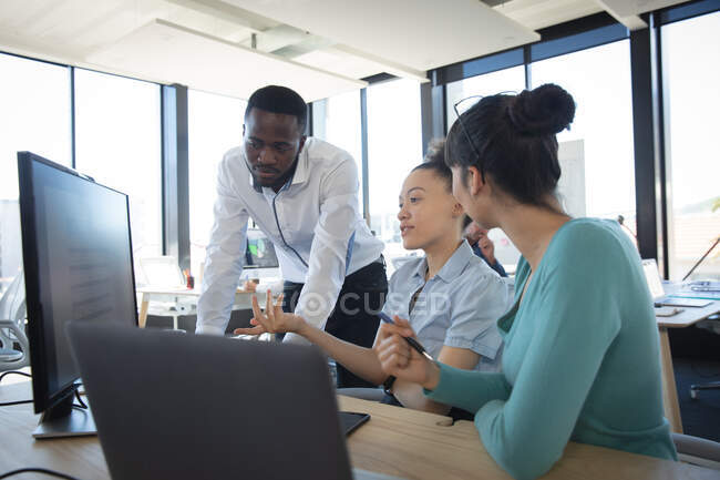 Multi-ethnic group of male and female colleagues working in a modern office, sitting at a desk, using a computer and discussing their work — Stock Photo