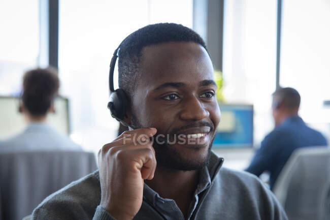 Крупный план афроамериканского бизнесмена, работающего в современном офисе, сидящего за столом, в наушниках и разговаривающего, со своими коллегами, работающими на заднем плане — стоковое фото