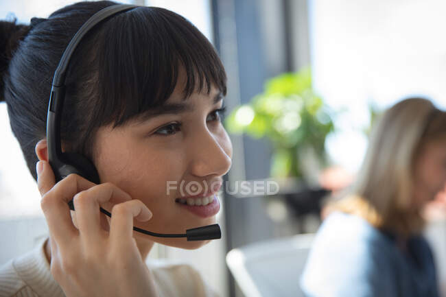 Close up of an Asian businesswoman working in a modern office, sitting at a desk, wearing headset and talking, with her colleague working in the background — Stock Photo